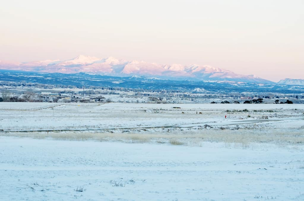 Snowy view of snow capped mountains and the valley below.