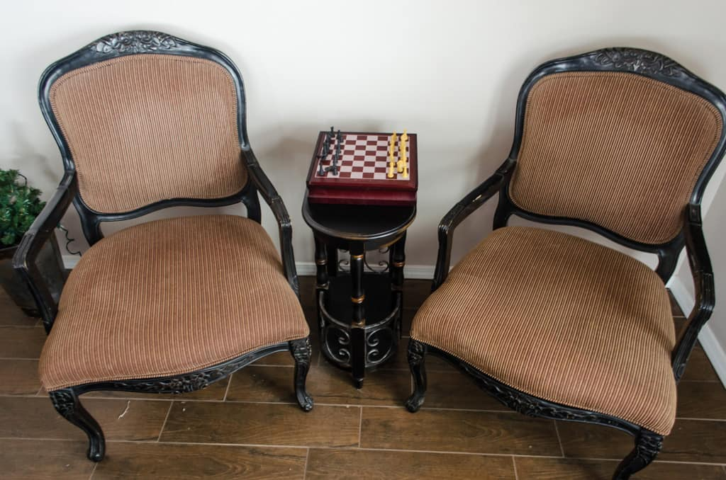 2 brown, vintage chairs with a table inbetween with a chess set on the table.