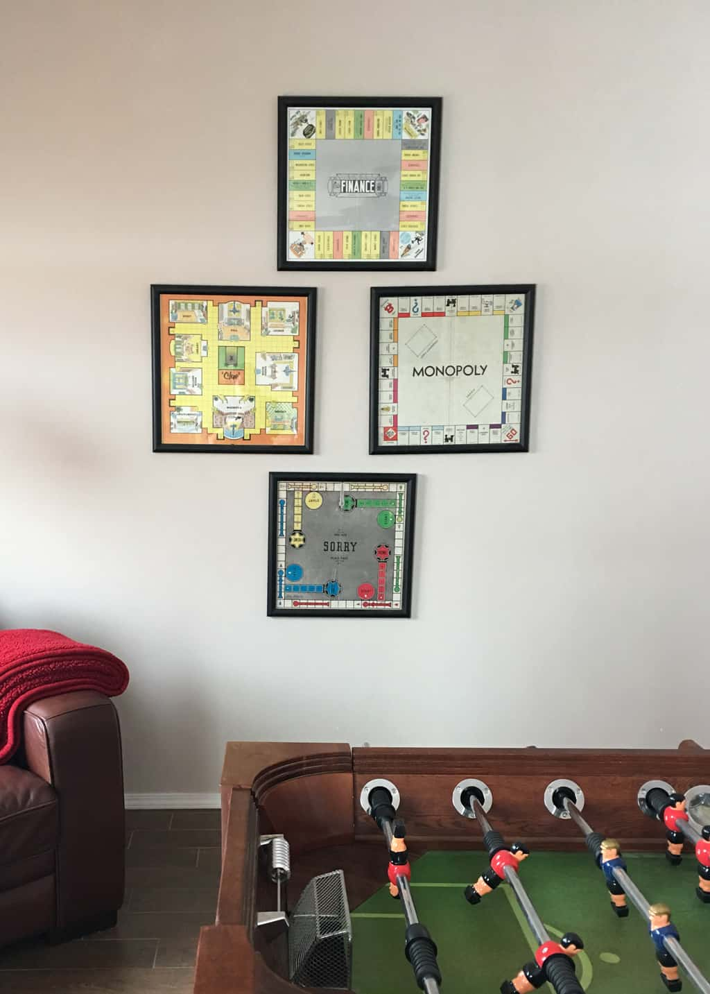 photo of a game room with a fooseball table and old game boards hung on the wall.