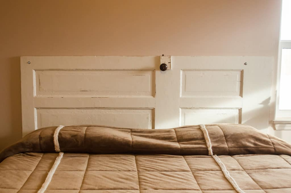 a photo of a bed with an old door as the backboard.