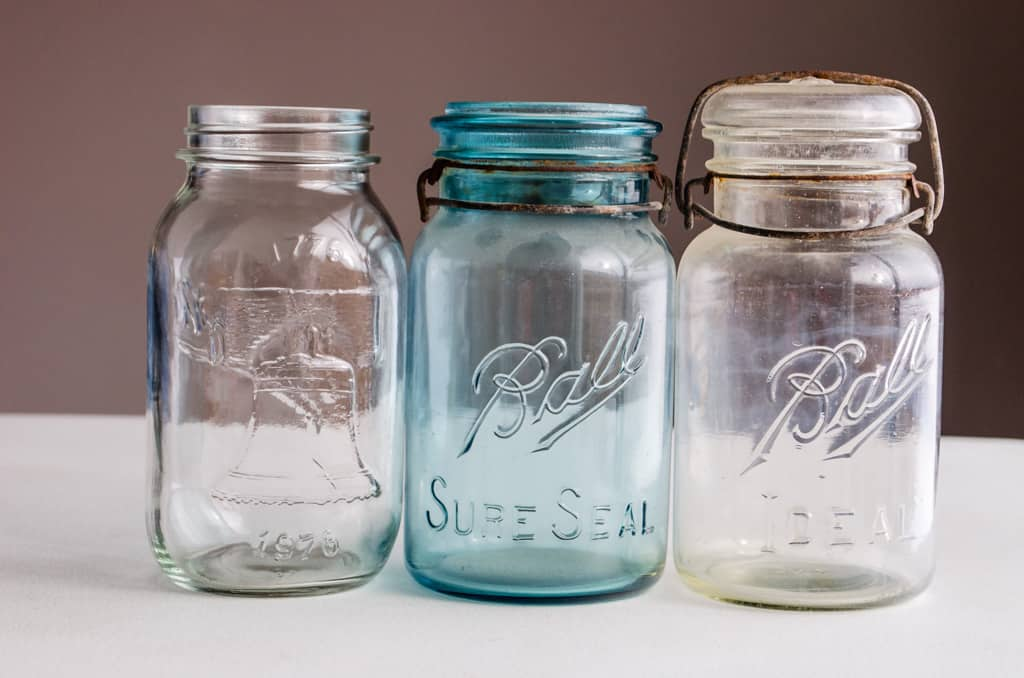3 old mason jars lined up on a table.
