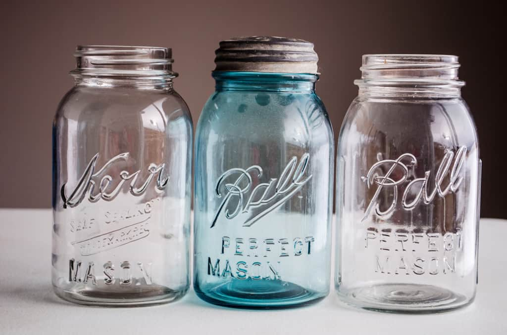 3 old mason jars lined up on a table