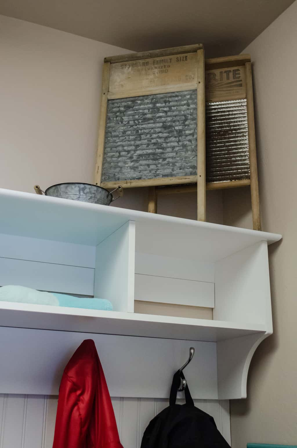 old washboards as decoration above a shelf in a laundry room