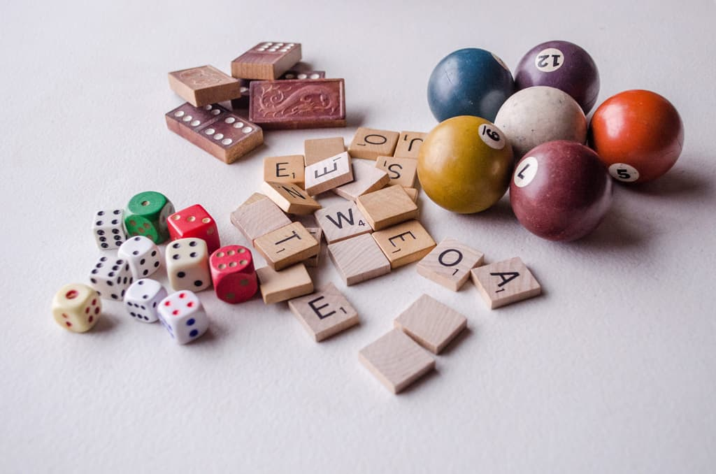 old game pieces, dice and pool balls on a table