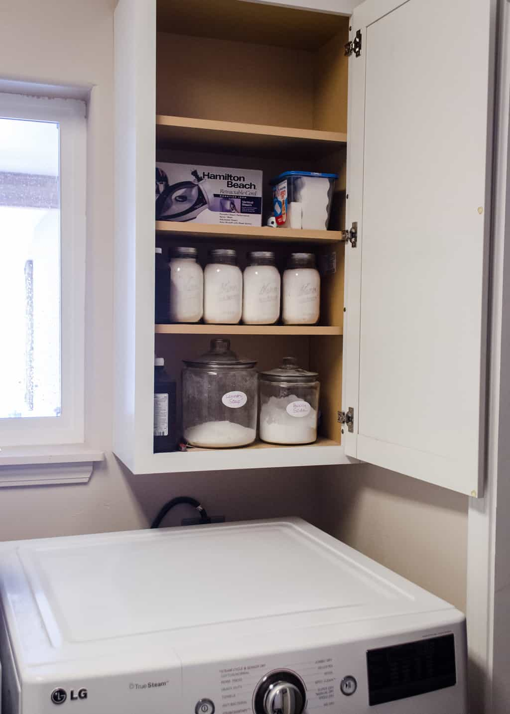 photo of inside a cabinet in a laundry room with jars of laundry soap inside