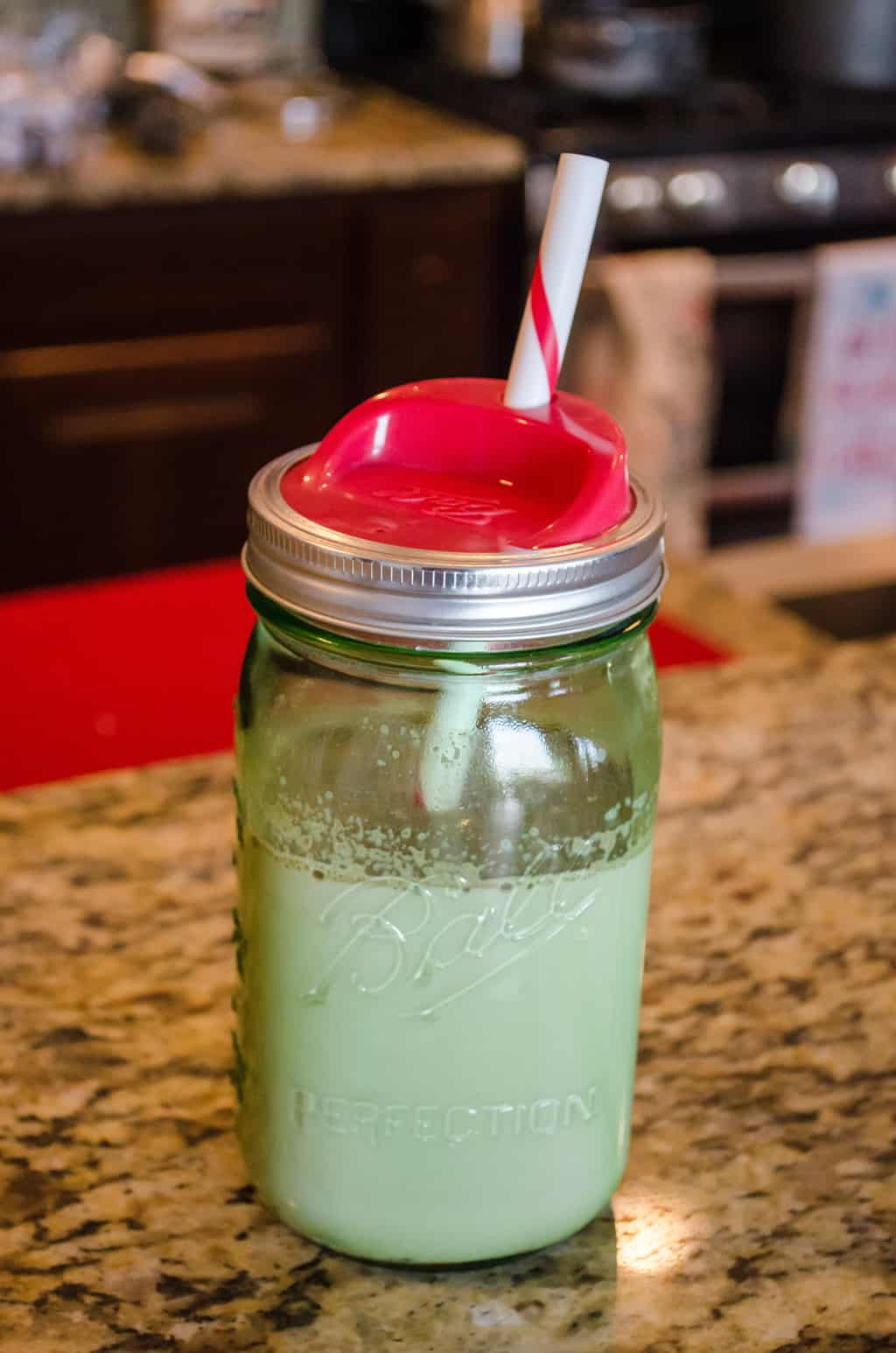 green mason jars with lid and straw with milk inside