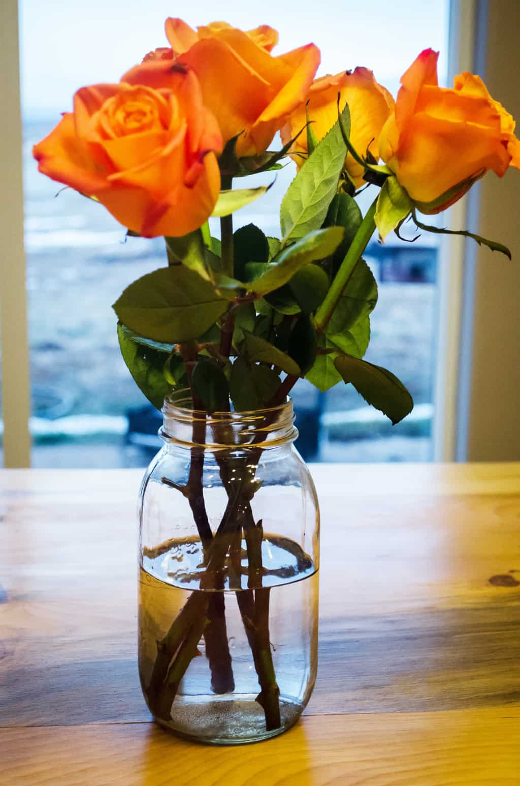 photo of mason jar vase with orange flowers on a wood table