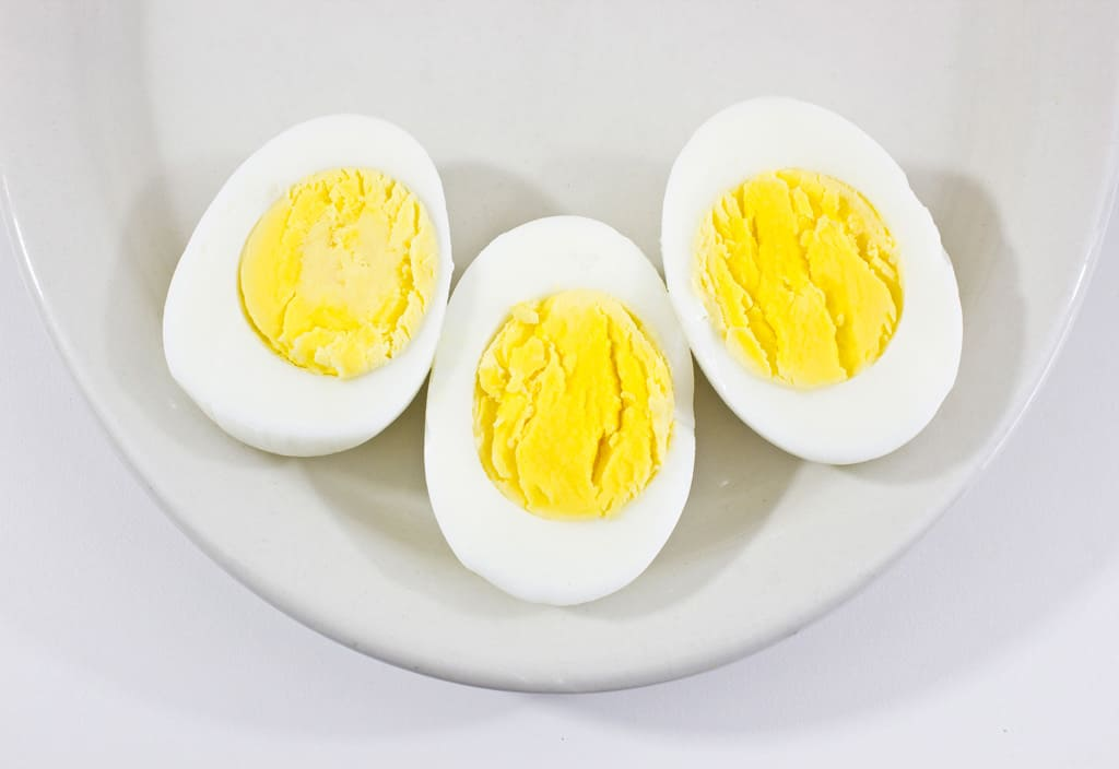 boiled eggs, peeled and cut in half on a plate