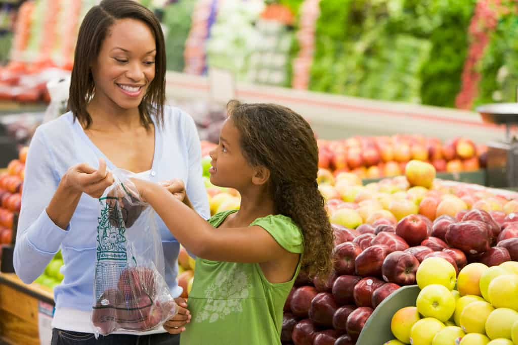 mother and daughter shopping for apples at the grocery store