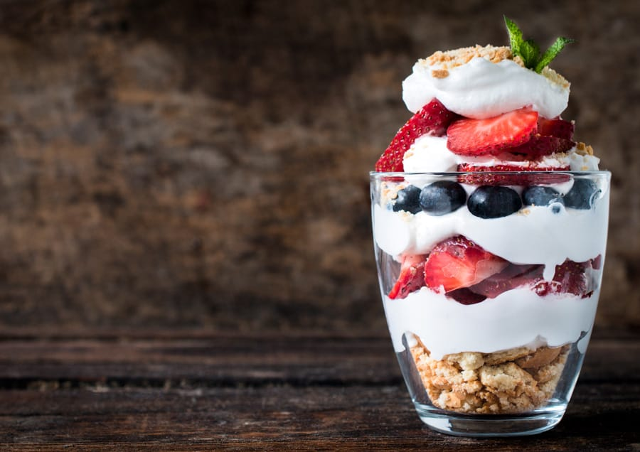 a clear glass of fruit and yogurt parfait
