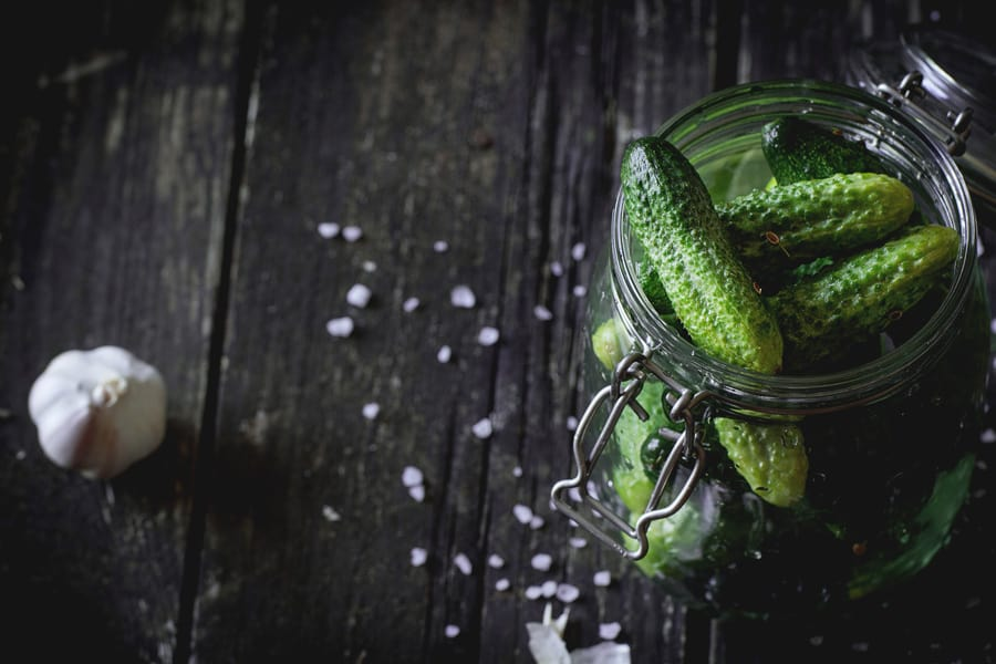 a mason jar full of pickles on a wooden background