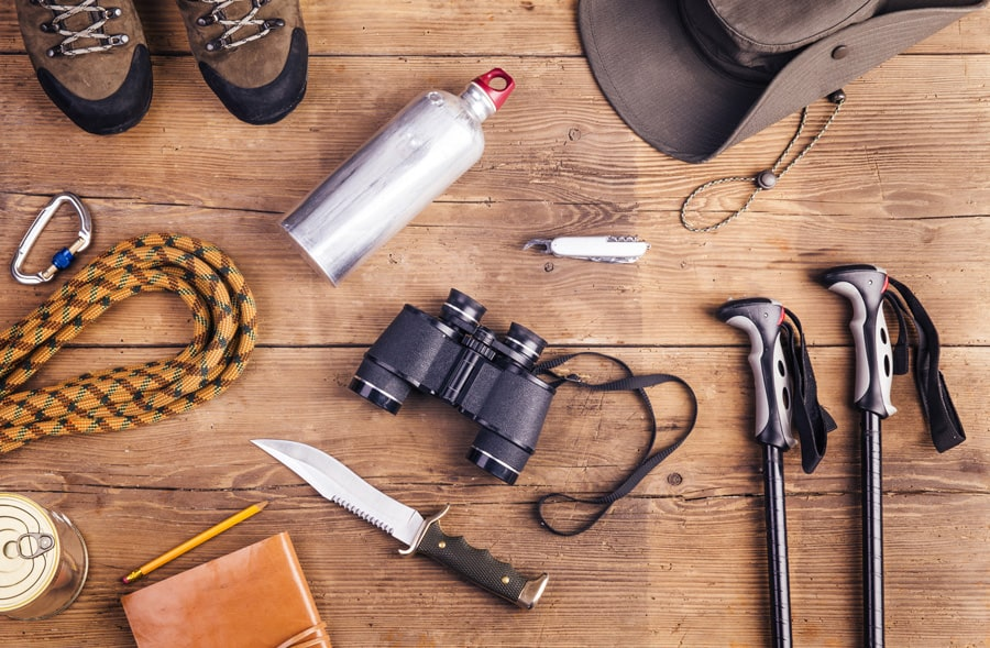 hiking and survival gear against a wooden background