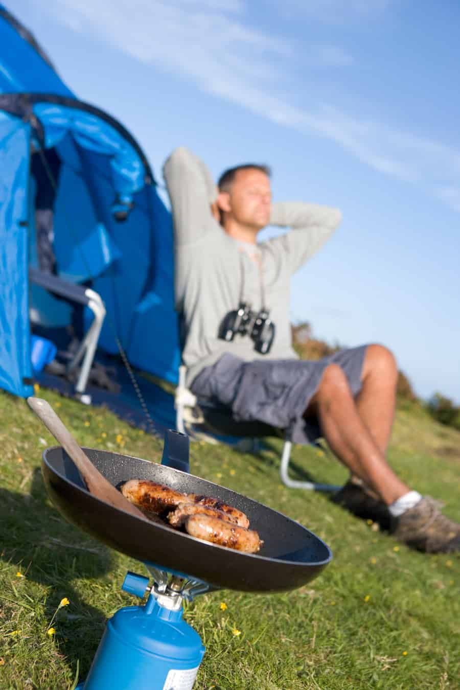a man camping and cooking with a portable stove
