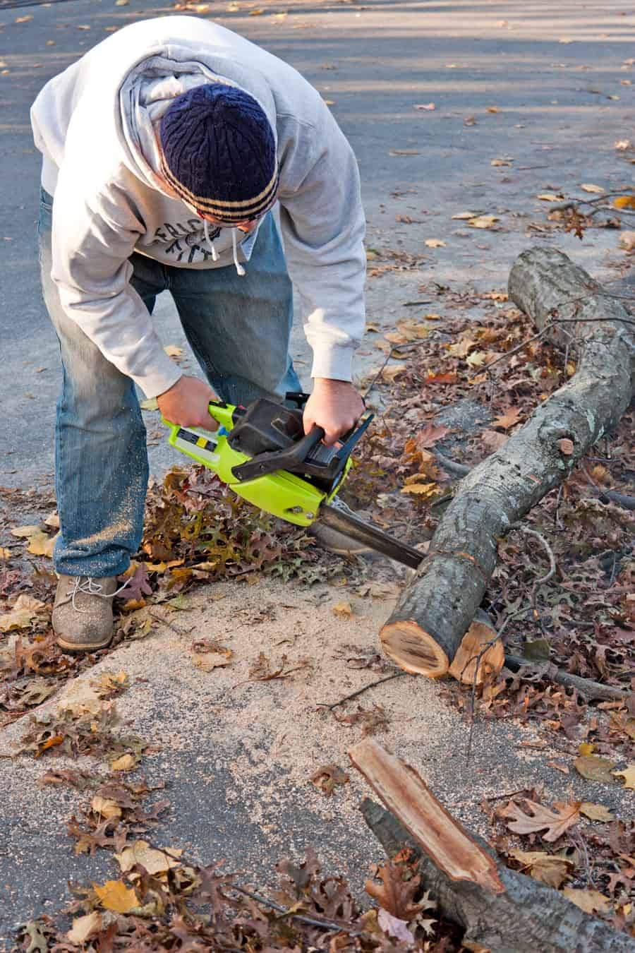 a man cutting up a down tree with a chainsaw