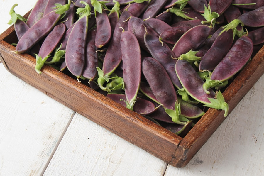 wooden box with purple peas inside