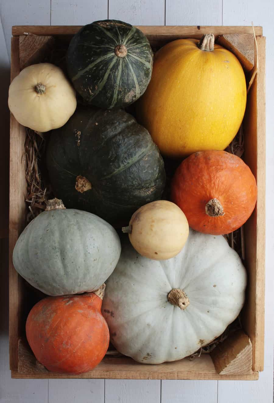 variety of pumpkins in wooden box