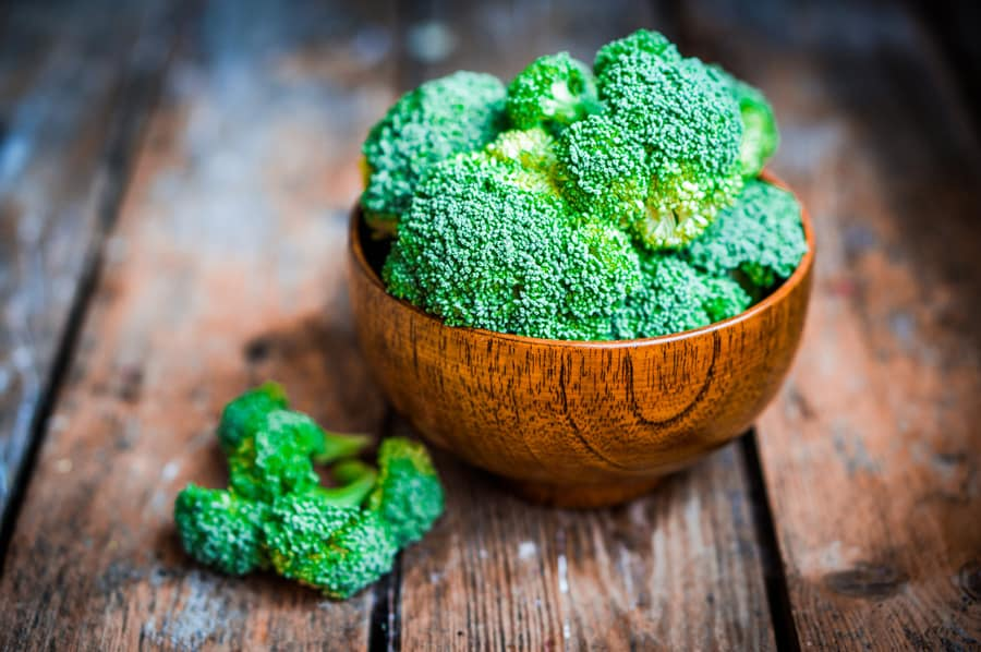 a wooden bowl of broccoli on a wooden background