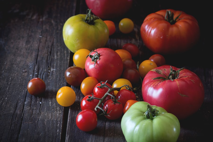 different types of tomatoes on a wooden background