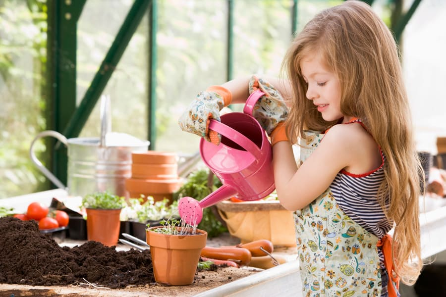 little girl watering a garden pot in a greenhouse