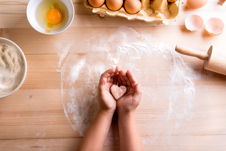 a baking scene with little hands holding a heart