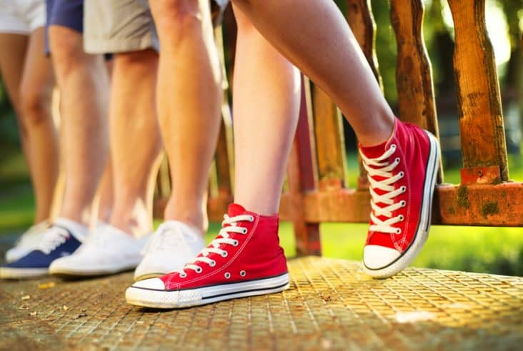 legs and shoes of people standing on a porch outside