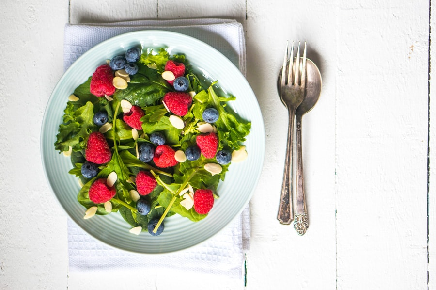 plate of salad with fruit on white background