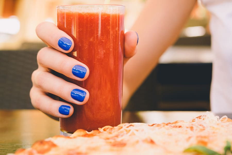 woman with blue manicure holding a glass of tomato juice