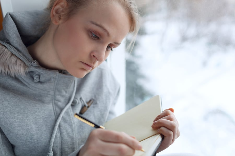 girl writing in a journal