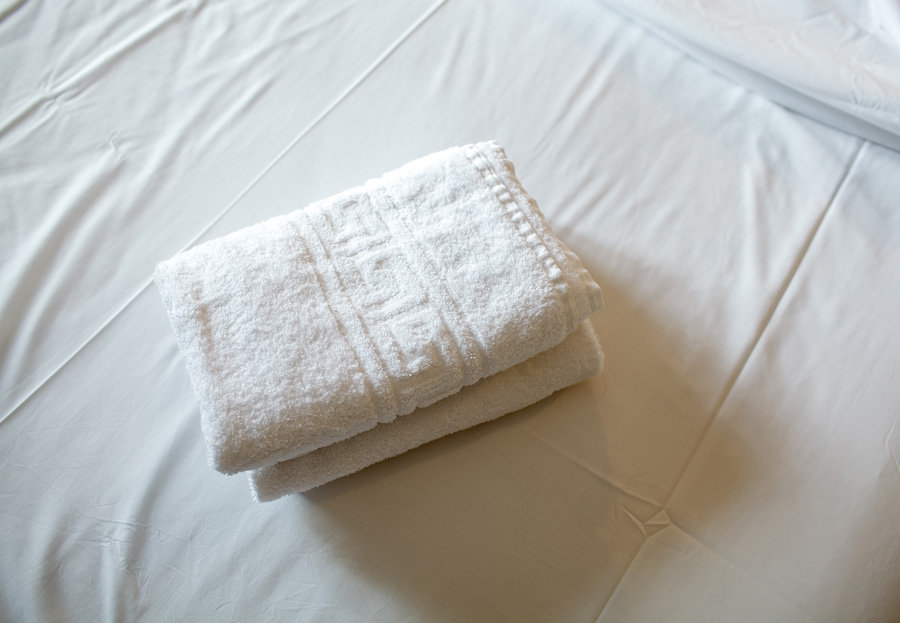 white sheets and folded white towels