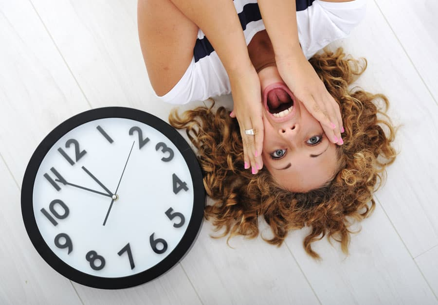 worried girl laying by a clock