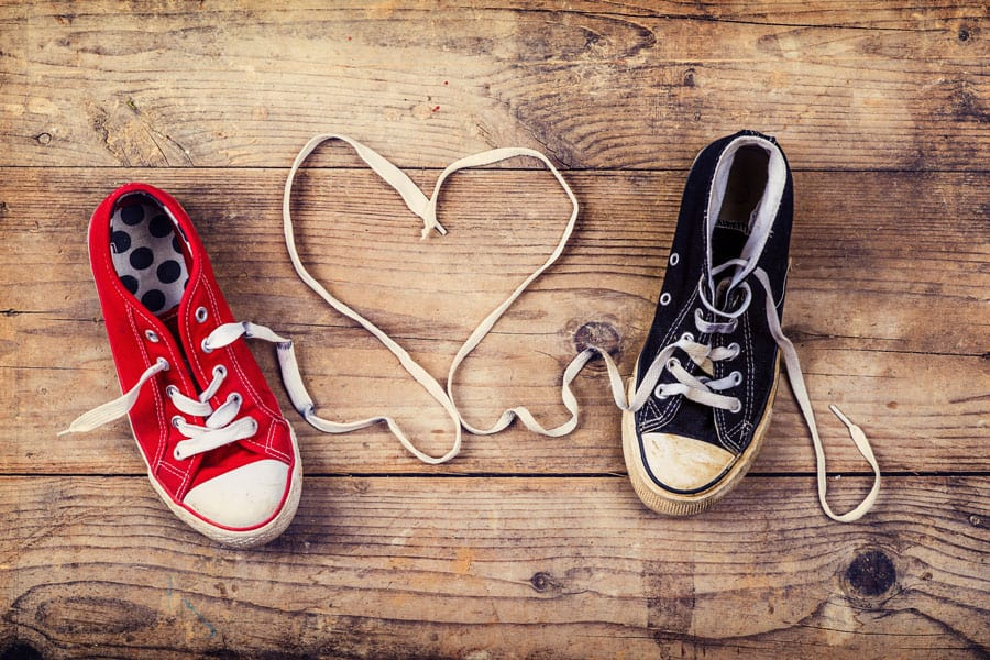 black and red shoe with laces tied in a heart