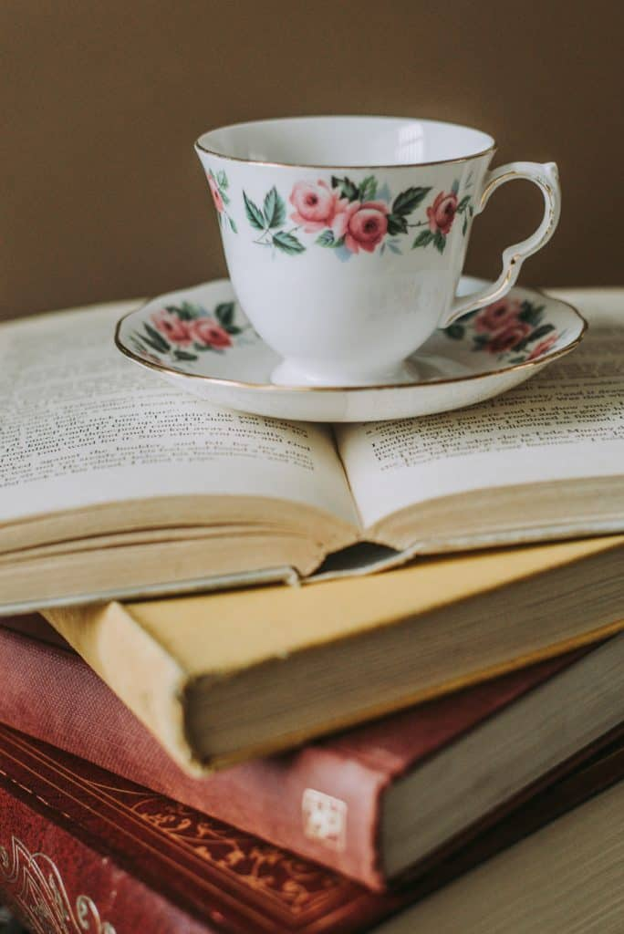 tea cup on top of stack of books
