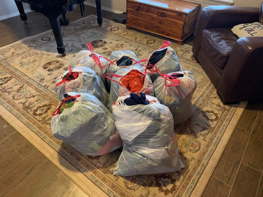 8 bags of clothes on the living room floor