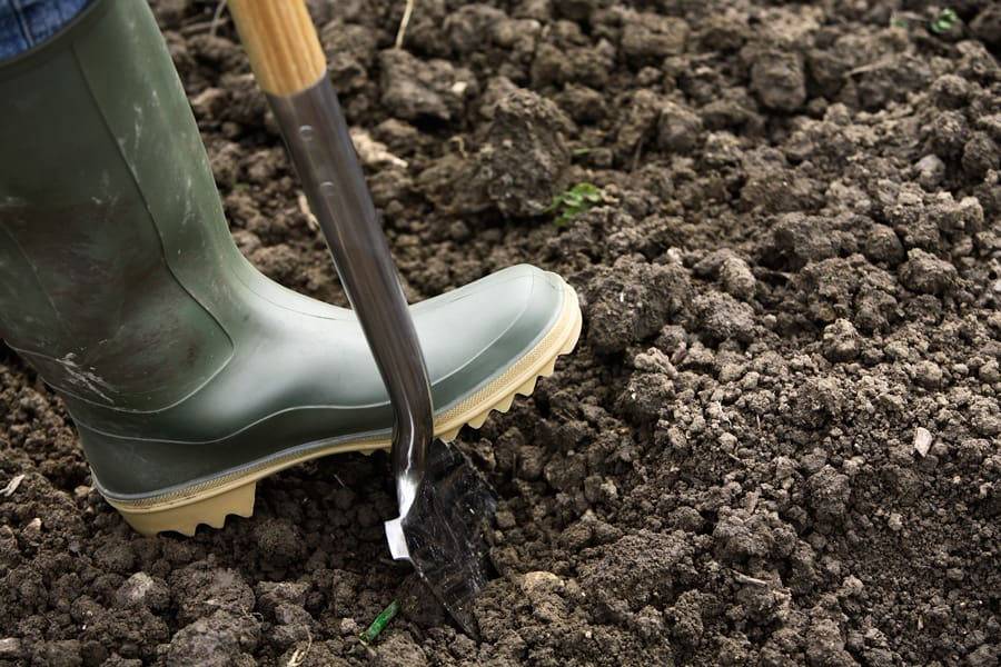 work boot in dirt with shovel