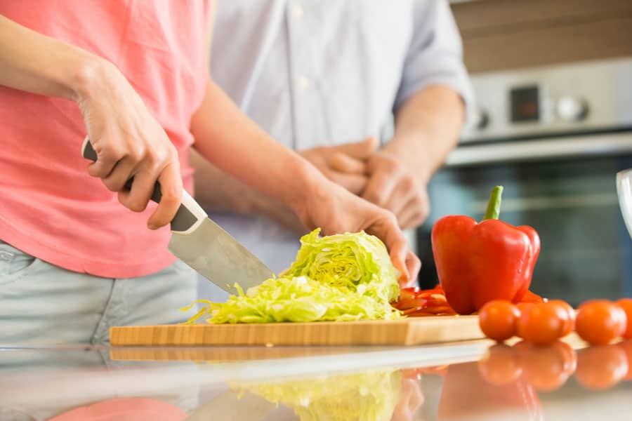 man and woman in the kitchen chopping veggies