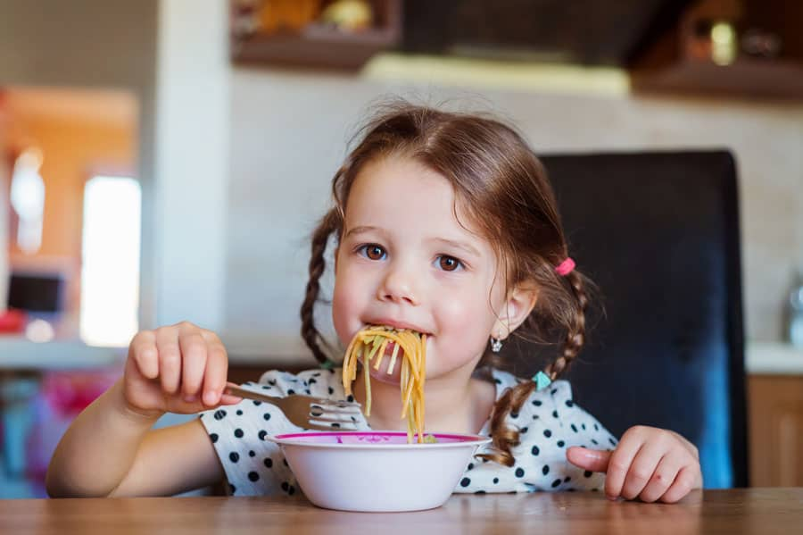little girl eating spaghetti