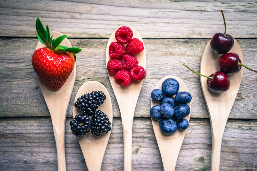 different types of fruit in wooden spoons