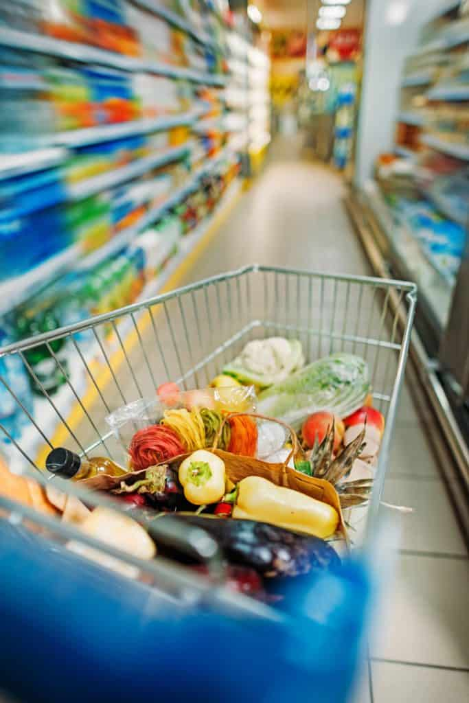 grocery cart full of food in grocery store aisle