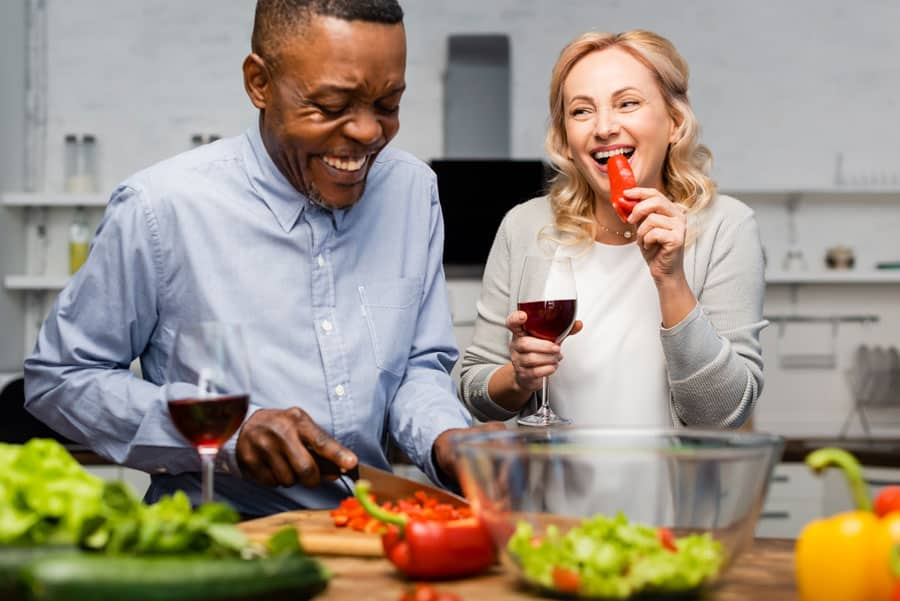 man and woman eating vegetables in kitchen
