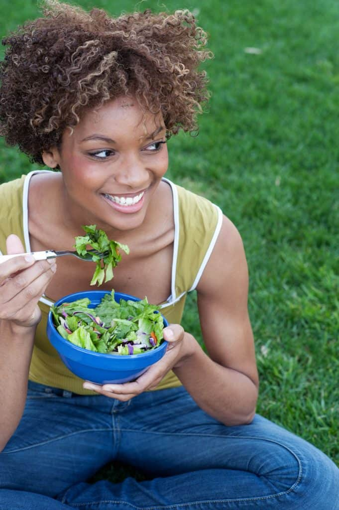 woman eating salad outside in the grass