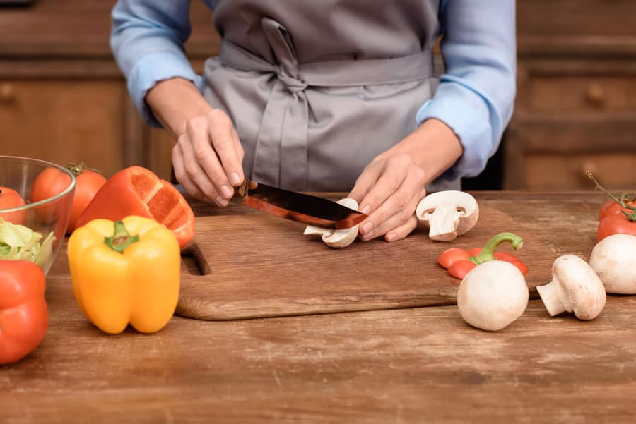 woman in kitchen chopping vegetables on wooden table