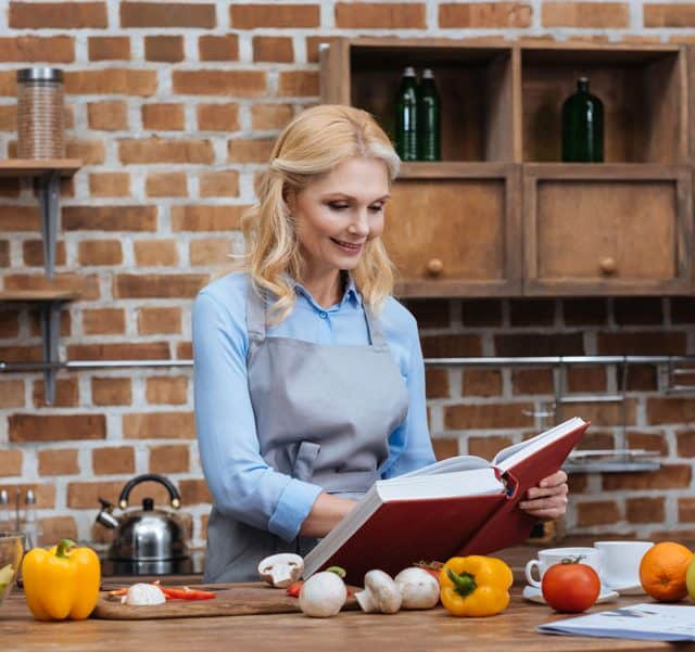 woman in kitchen cooking healthy food with cookbook