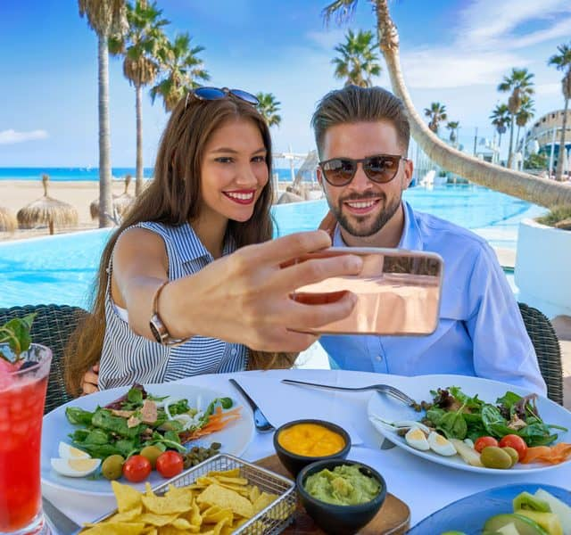 couple taking a selfie at the dinner table during vacation